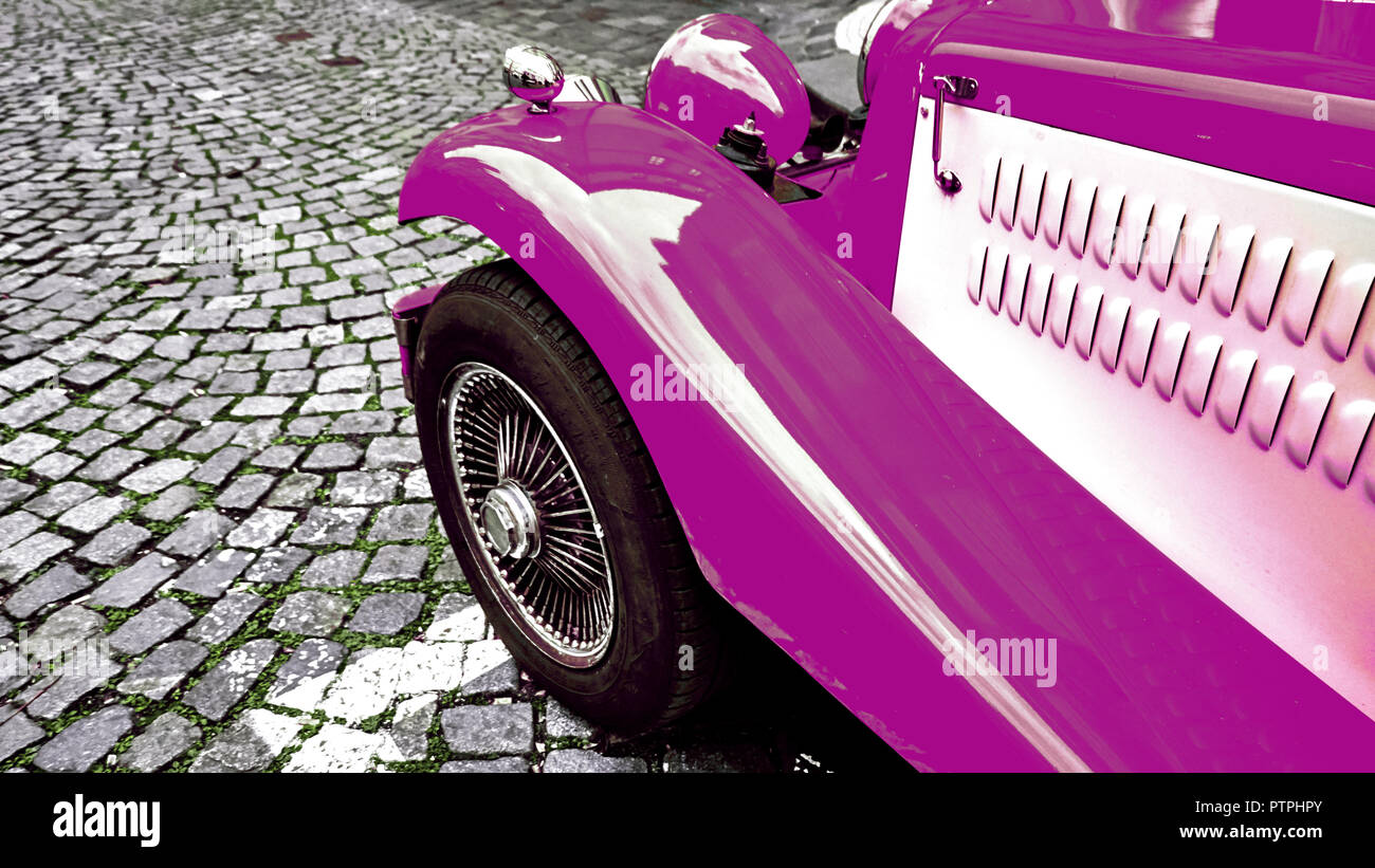 Front side part of vintage classic purple hot rod car on a cobble road. Stock Photo