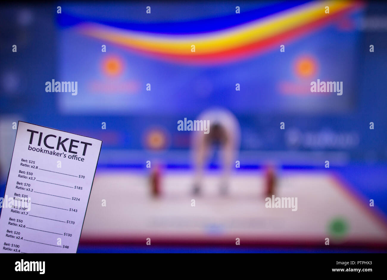 Bookmaker ticket on the background of TV on which show weightlifting, sports betting, barbell - Stock Image