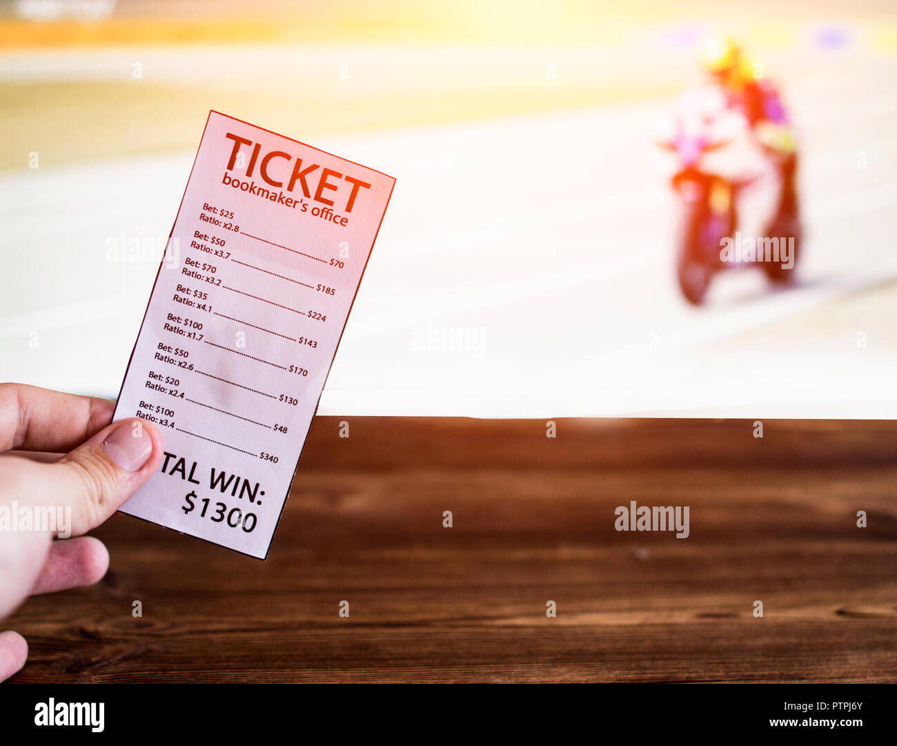 Bookmaker ticket on the background of the TV on which show motorcycle racing, sports betting, Bookmaker ticket and motorcycle races - Stock Image