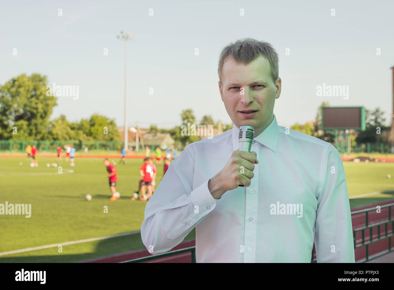 A male commentator in a white shirt with a microphone comments on football in the background of a football match - Stock Image