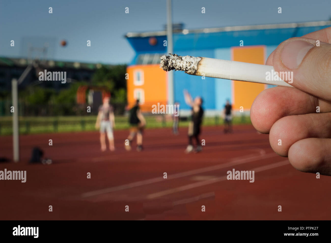 A man holds a cigarette in the background of the stadium where they play basketball, close-up, bad habit - Stock Image