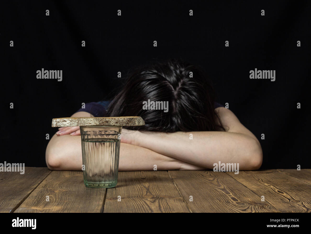 A glass of water and a piece of bread, the girl is lying on the table and lapachet, black background, sorrow - Stock Image