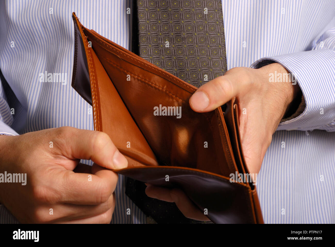 man showing an empty wallet, no money concept - Stock Image