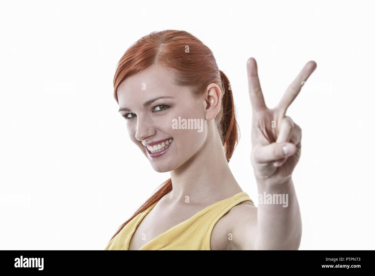 Junge rothaarige Frau zeigt Victory Zeichen, Young red-haired woman shows victory sign, attractive, beautiful, beauty, casual, caucasian, close, color - Stock Image