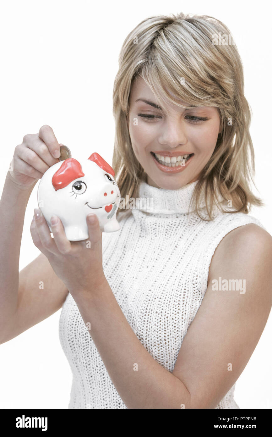 Frau, Sparschwein, halten, Geldstueck, einwerfen, Portrait, Frauenportrait, 20-30 Jahre, jung, blond, sparen, sparsam, Sparsamkeit, Vermoegensbildung, - Stock Image