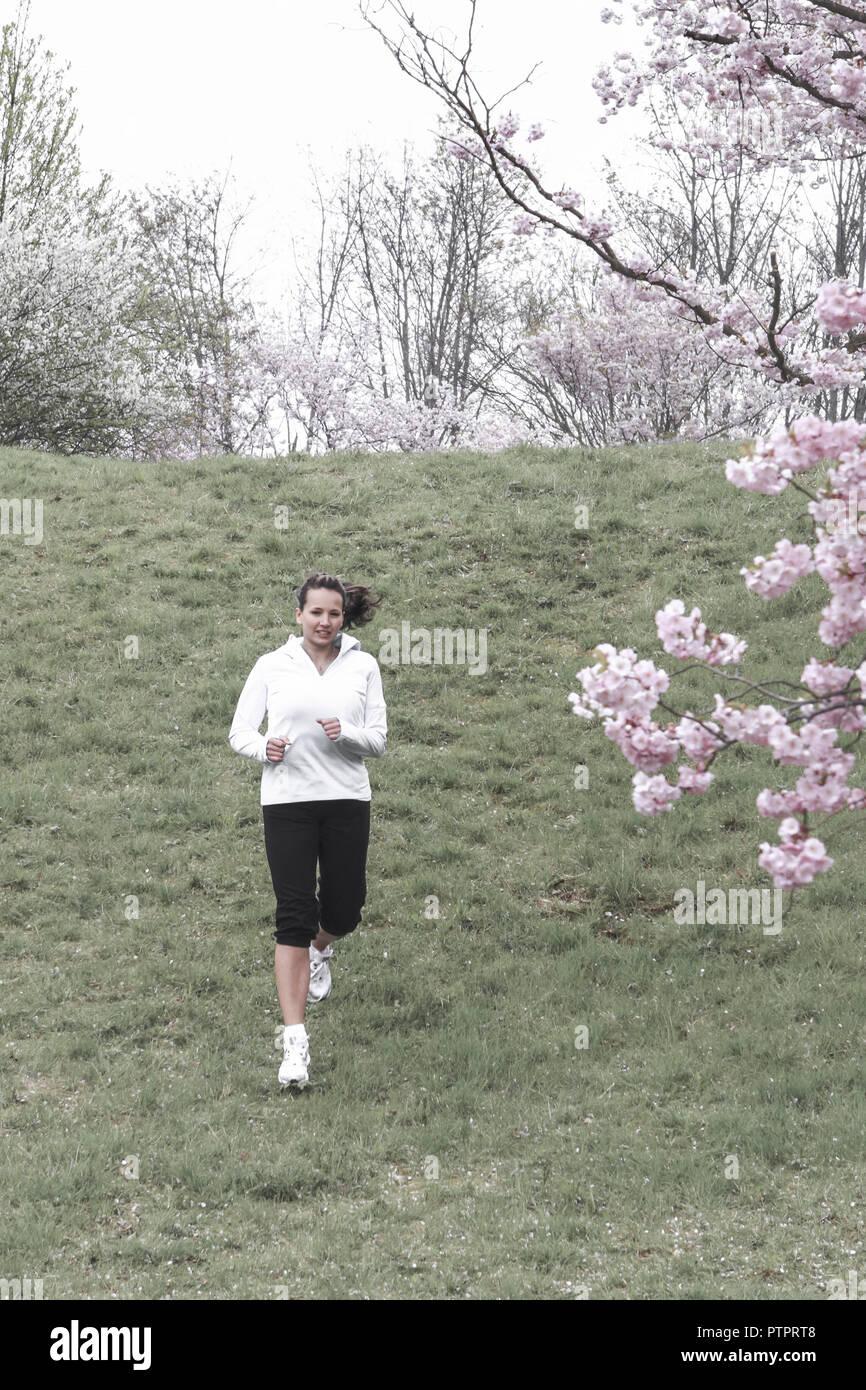 junge Frau beim Joggen im Fruehling, Baumbluete (Modellfreigabe) - Stock Image