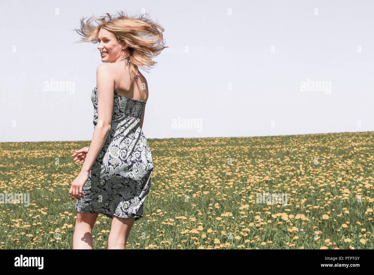 glueckliche junge Frau Fruehling, Blumenwiese, laufen, rennen, tanzen (Modellfreigabe) - Stock Image