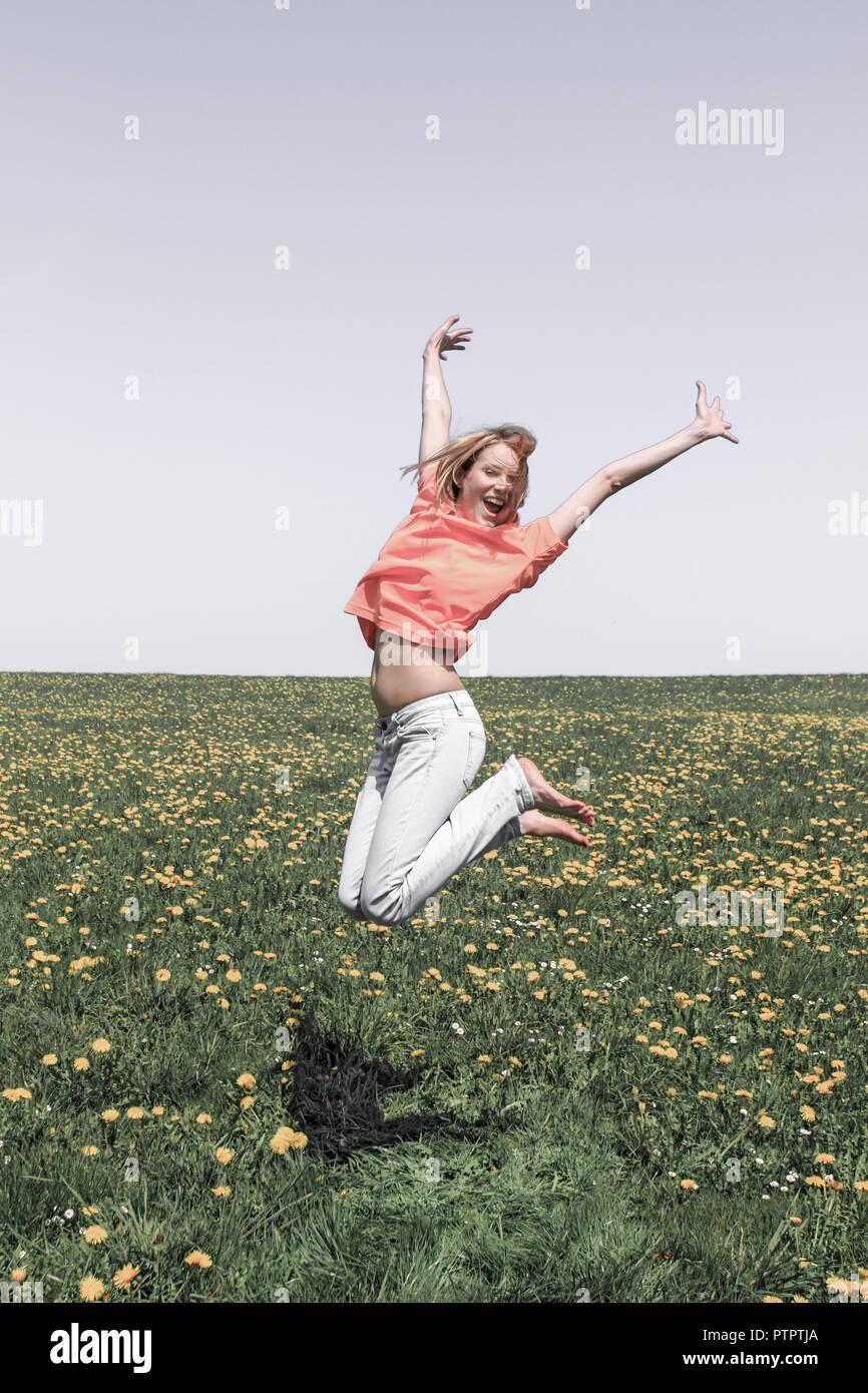 glueckliche junge Frau Fruehling, Blumenwiese, Freudensprung, Luftsprung (Modellfreigabe) - Stock Image