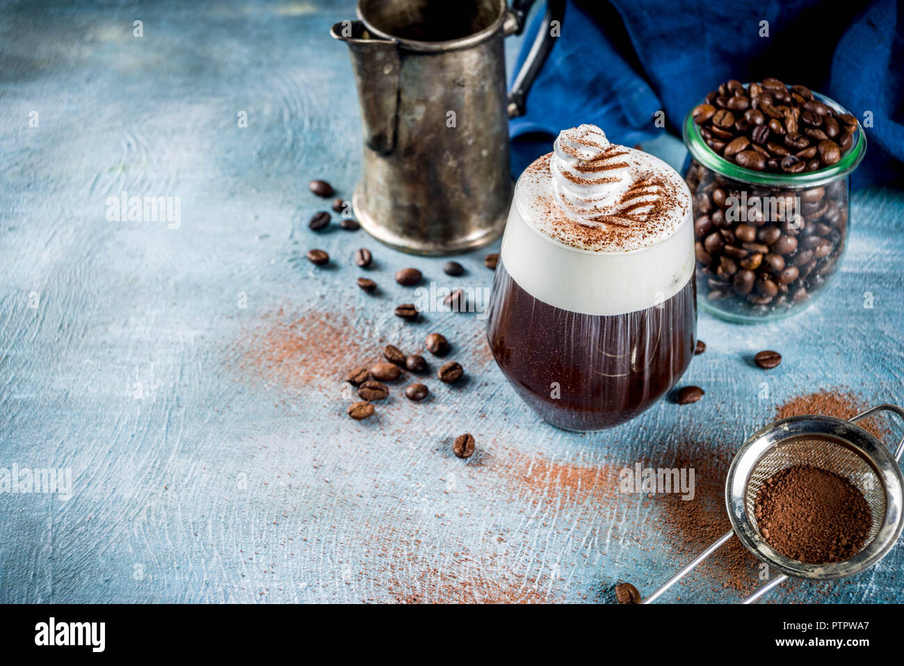 Autumn espresso drink ideas, Irish coffee cocktail with whipped cream and cocoa, blue concrete background copy space Stock Photo