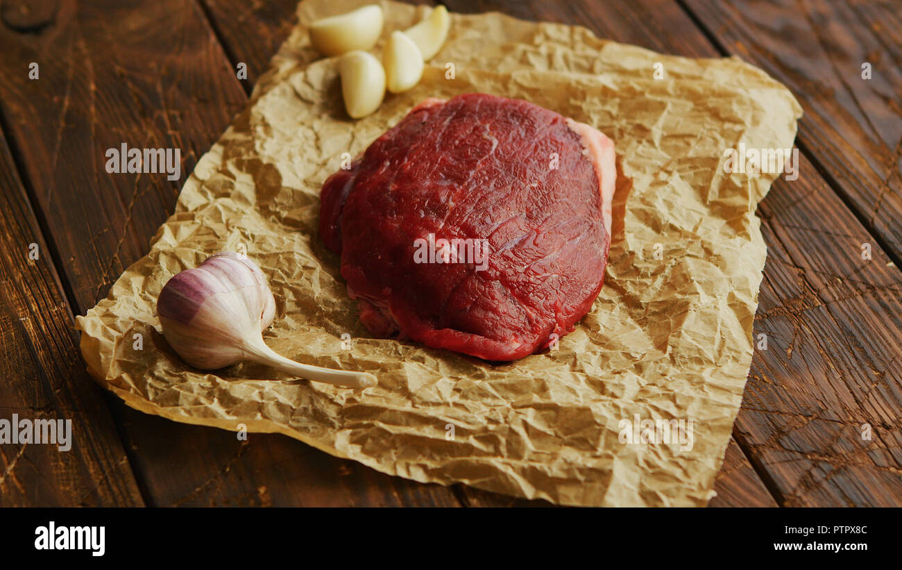 Garlic and meat on parchment - Stock Image