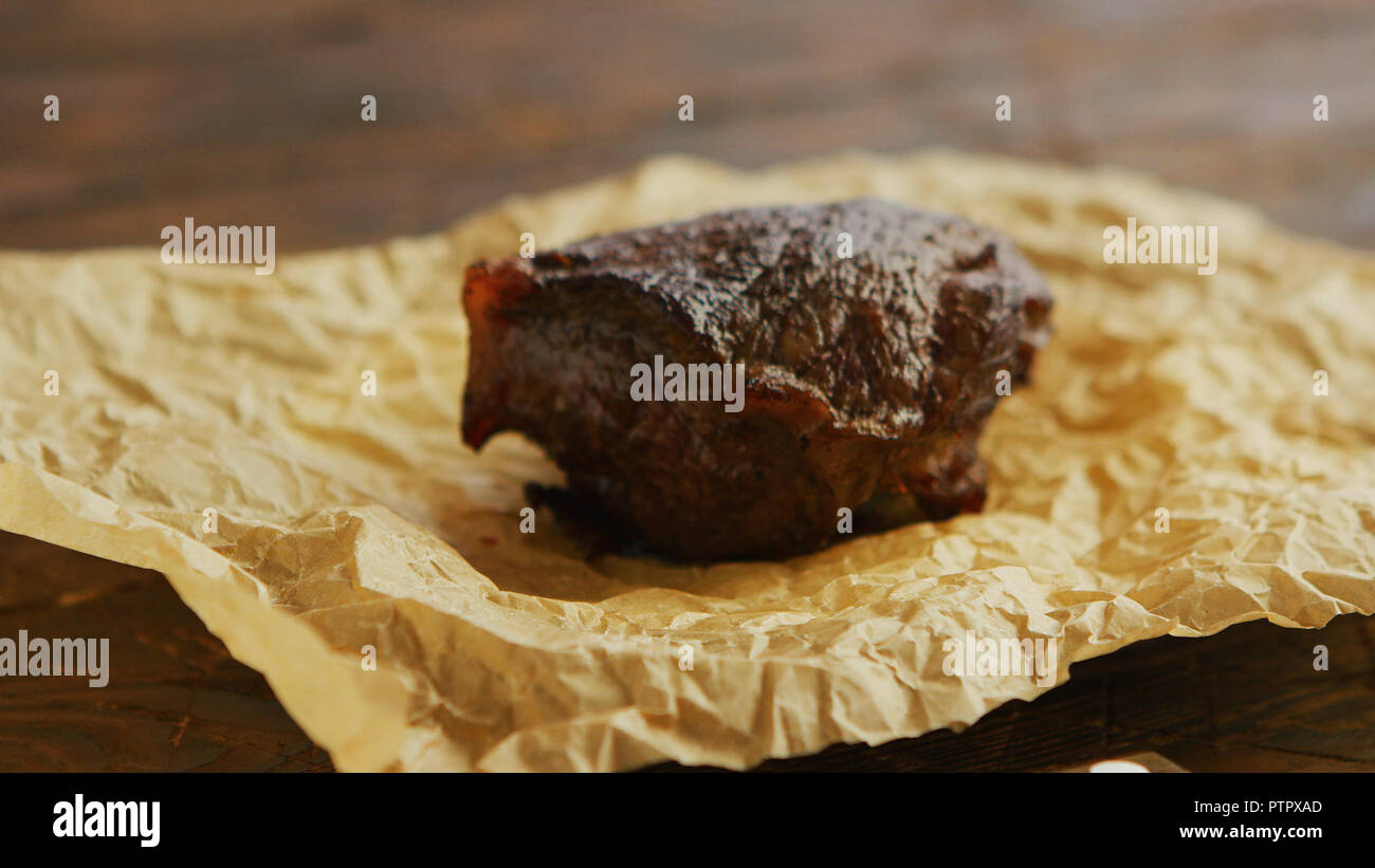 Piece of roasted meat on parchment - Stock Image