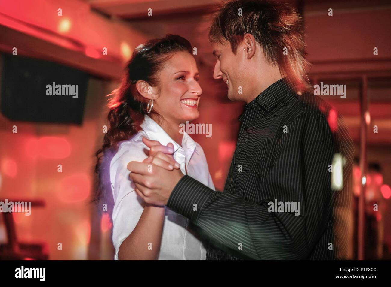 junges verliebtes Paar beim Tanzen in einer Disco (Modellfreigabe) - Stock Image