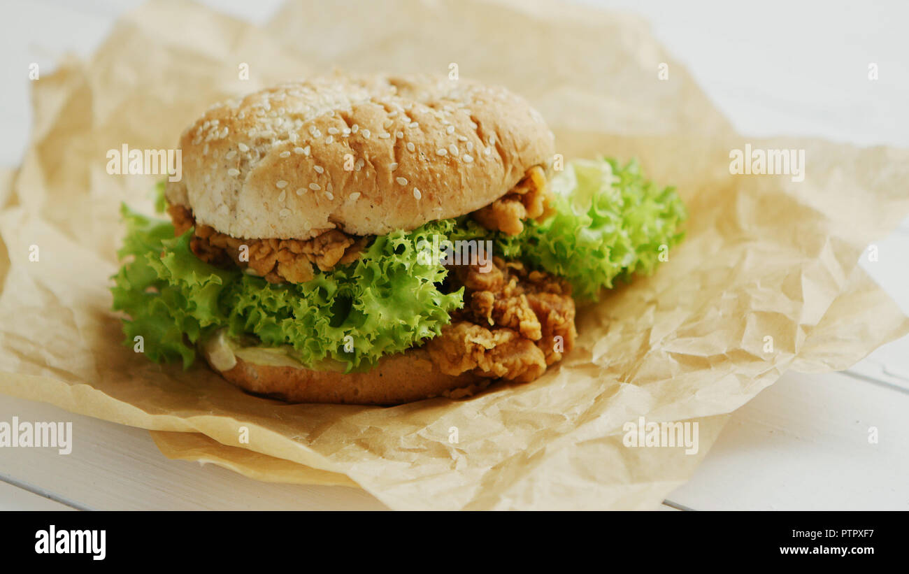 Chicken burger lying on parchment - Stock Image