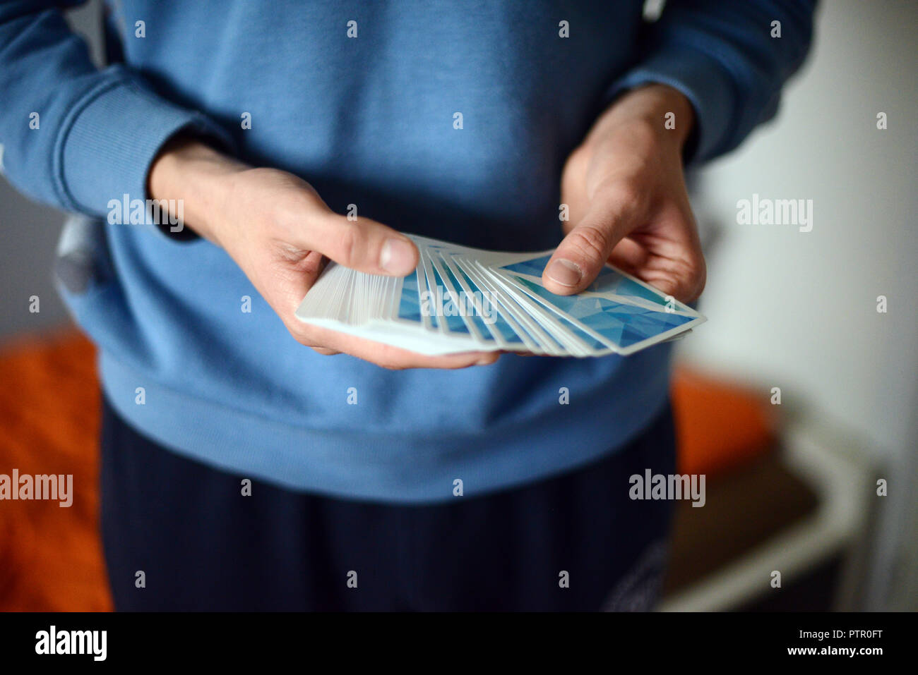 young man in blue sweater holding blue hobby cards in his hands - Stock Image