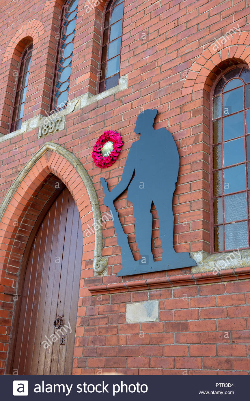 Remembrance display on a Methodist Church in Shropshire showing a soldier silhouette and poppy wreath. - Stock Image