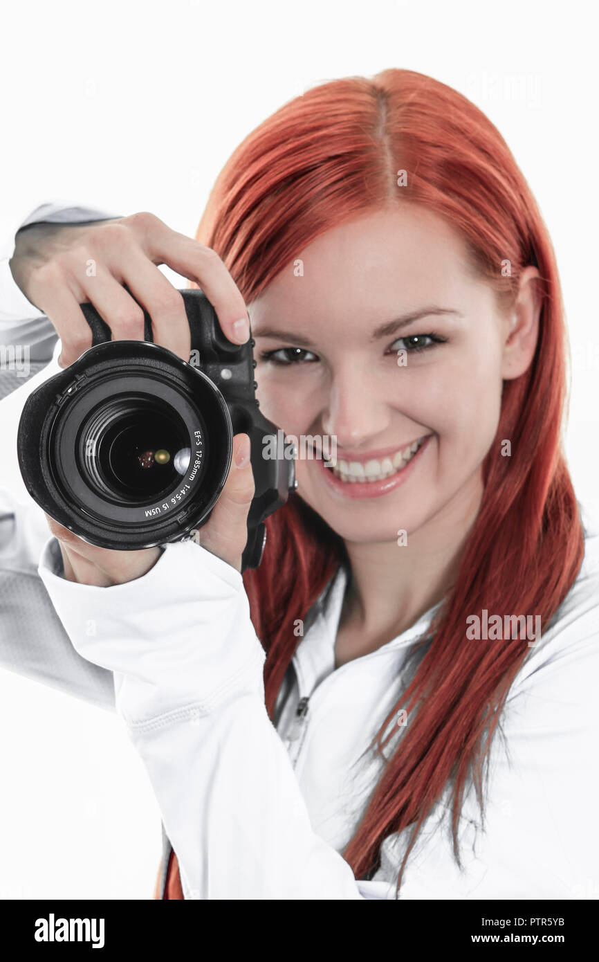 junge rothaarige Fotografin mit ihrer Kamera, Young woman photographer and her camera, attractive, beautiful, camera, casual, elegance, emotion, equip - Stock Image