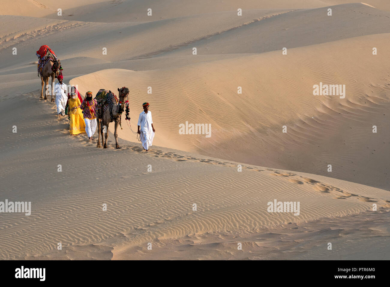 The image of Rajasthani trditional man and woman in sand dunes,  Jaisalmer, Rajasthan, India Stock Photo