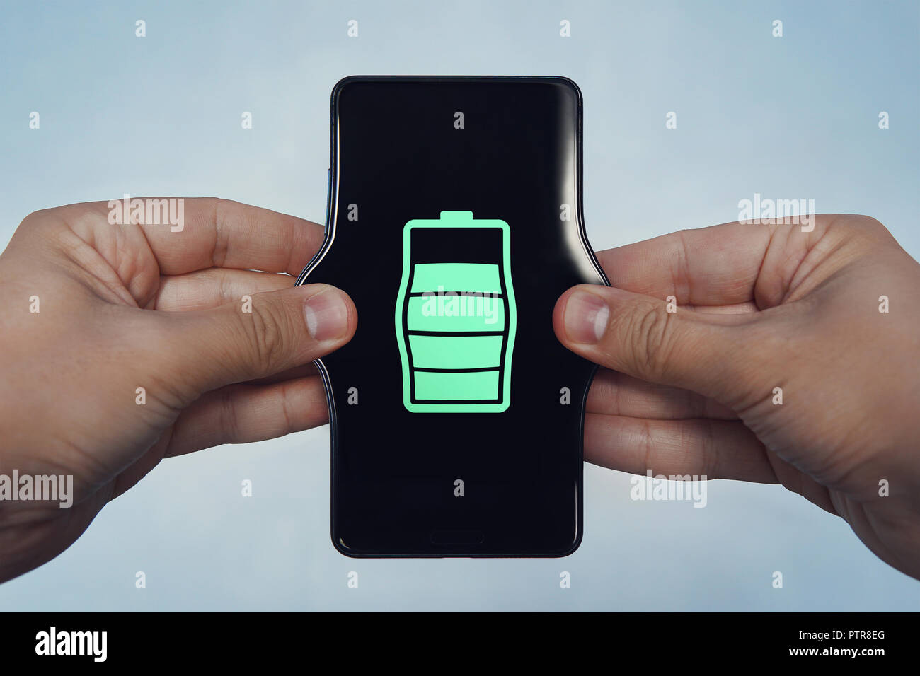 how to increase the performance of the smartphone, increase the battery level, stretch the phone, a man stretches the phone with his hands - Stock Image