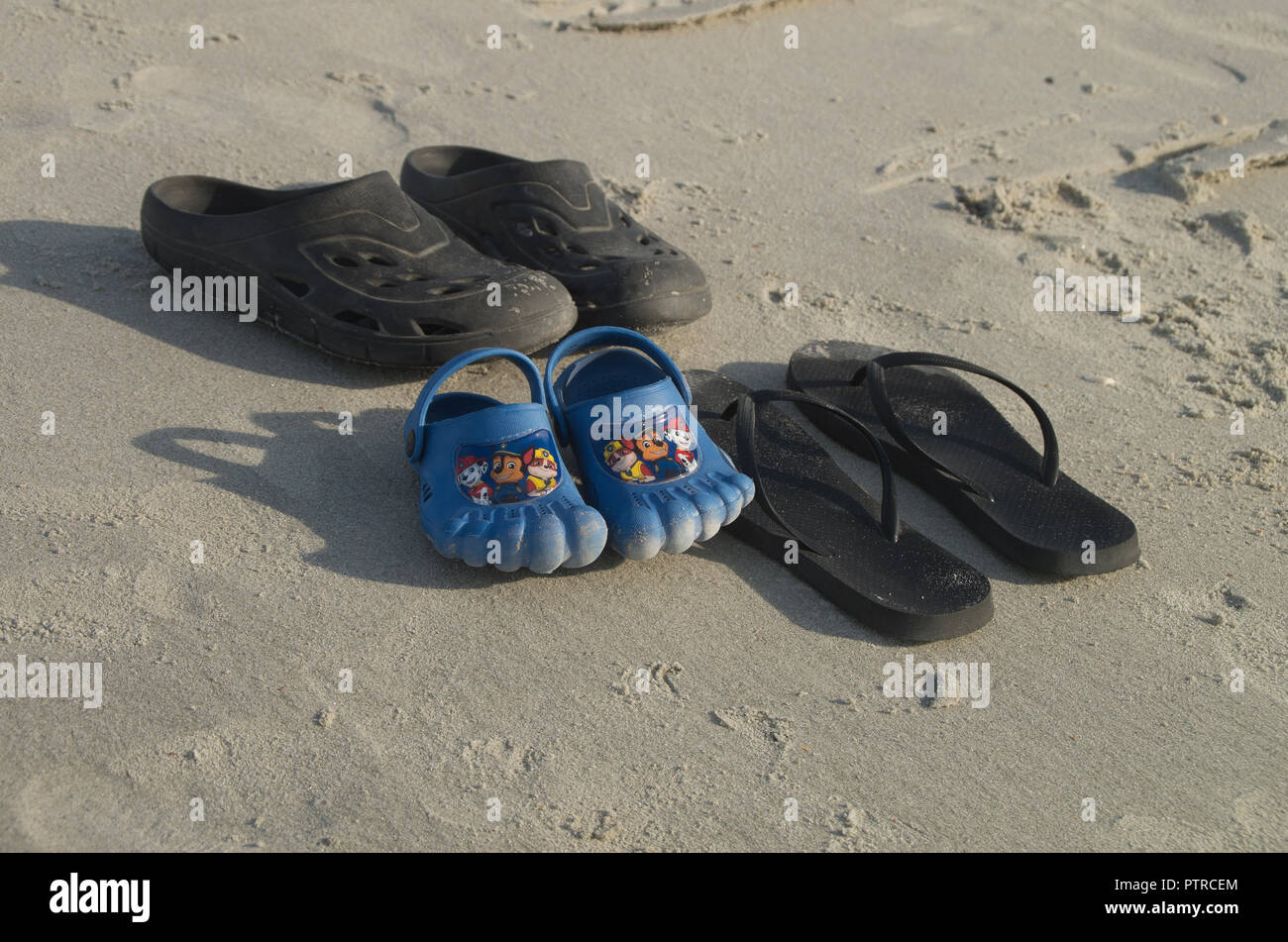 A group of shoes rests on the sand for a family to return in Myrtle Beach South Carolina - Stock Image