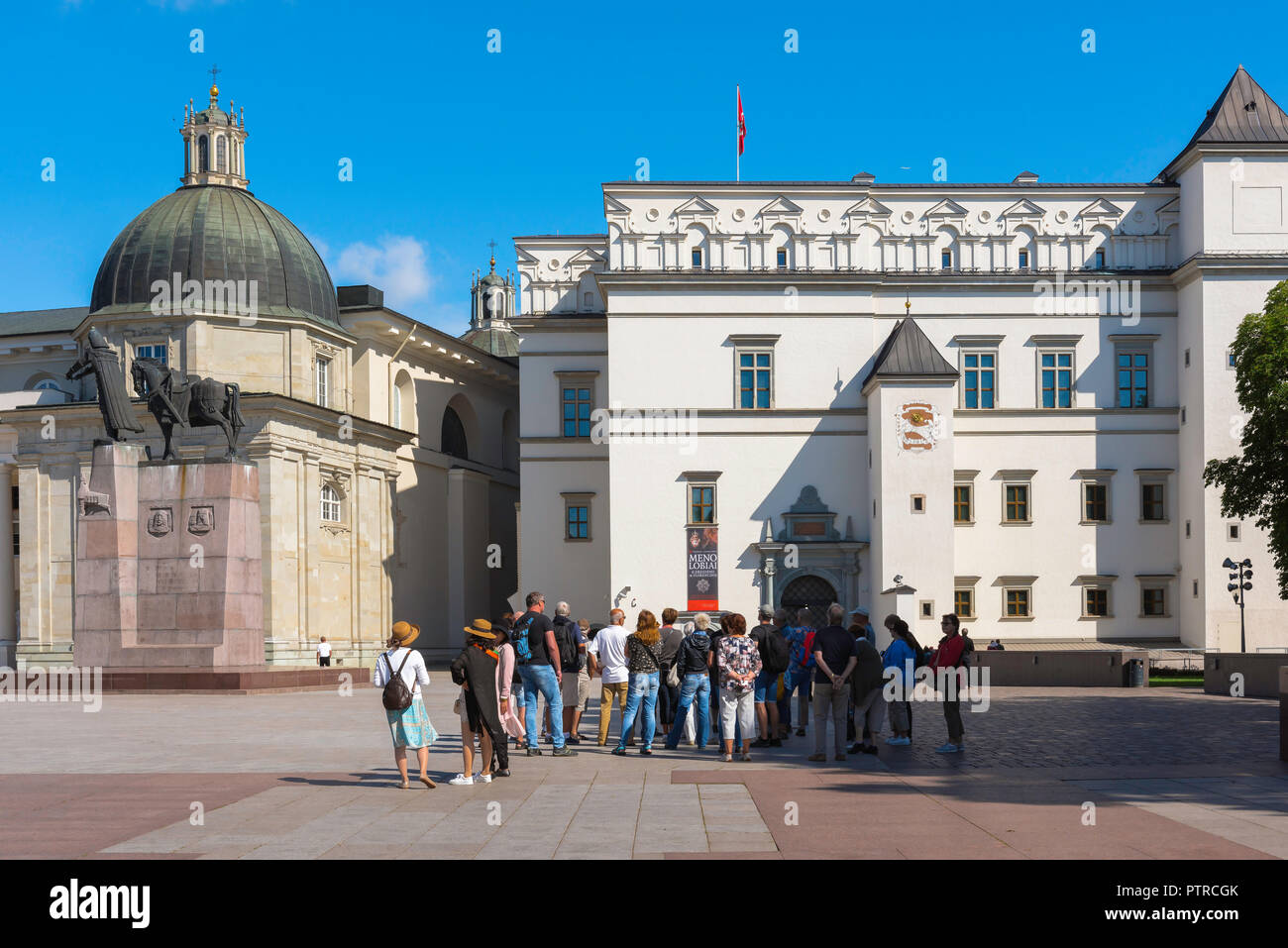 Tourism tourists europe, a tour group stands in Cathedral Square in Vilnius on a summer morning looking at the Palace of the Grand Dukes of Lithuania. - Stock Image