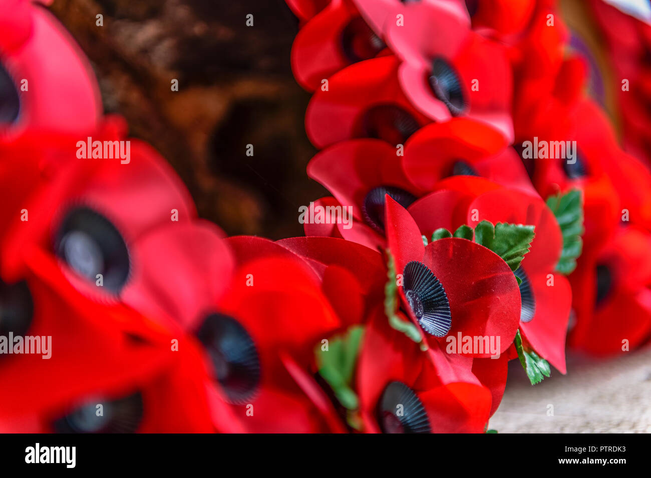 A Poppy Wreath laid at the foot of a World War Remembrance monument. Stock Photo