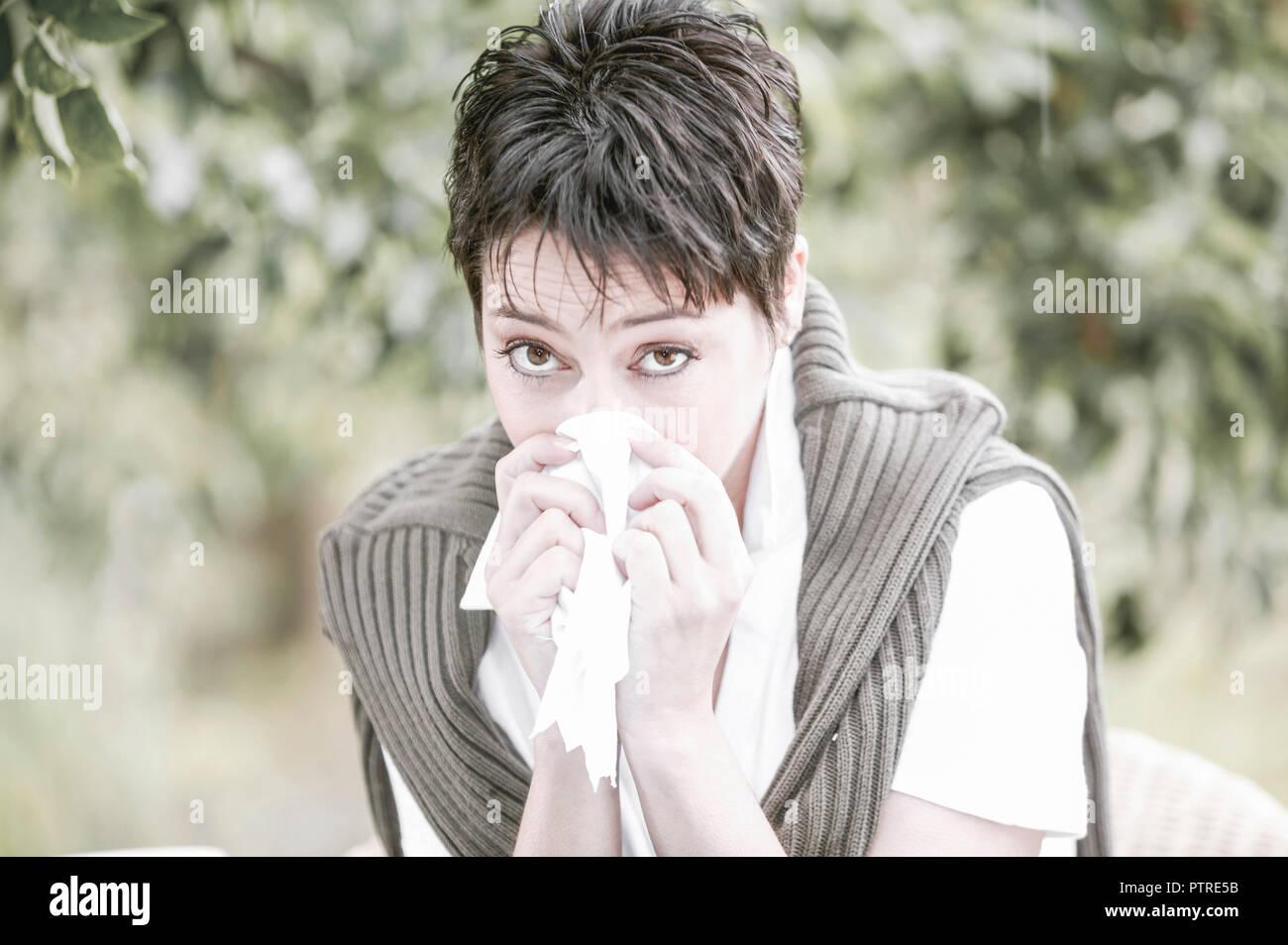 Frau, jung, Taschentuch, schnaeuzen, Portrait, aussen, Sommer, Fruehling, Park, Garten, Pollen, Pollenflug, 30-40, 20-30 Jahre, Allergie, Erkaeltung,  Stock Photo