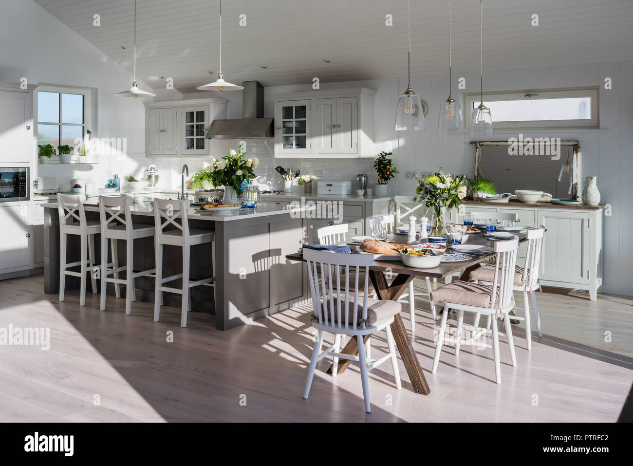 Open Plan Kitchen And Dining Room With Sea Views Bar Stools At Island Unit  With Dining Table And Chairs In Sunlit Coastal Home
