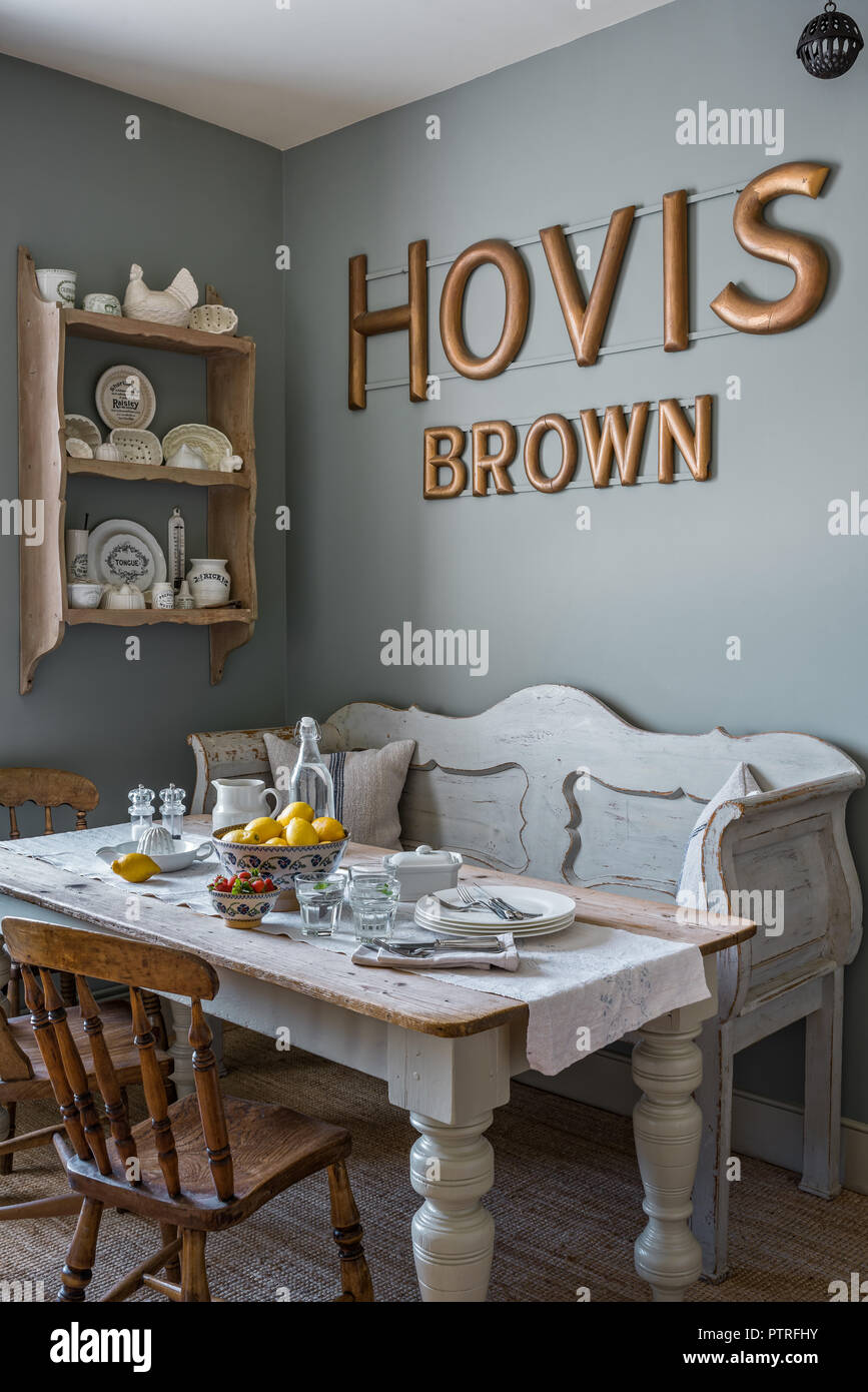 16th century farmhouse renovation 'HOVIS' lettering above bench seat and table with vintage crockery on wall mounted shelves in restored 16th century  - Stock Image