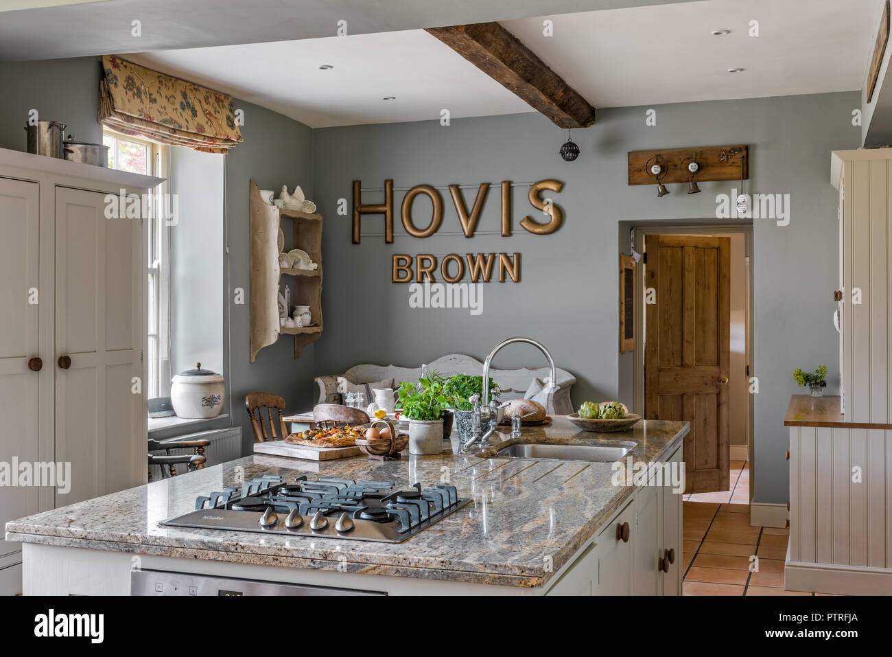 'HOVIS' lettering in kitchen with gas hob fitted to island unit in restored 16th century farmhouse - Stock Image