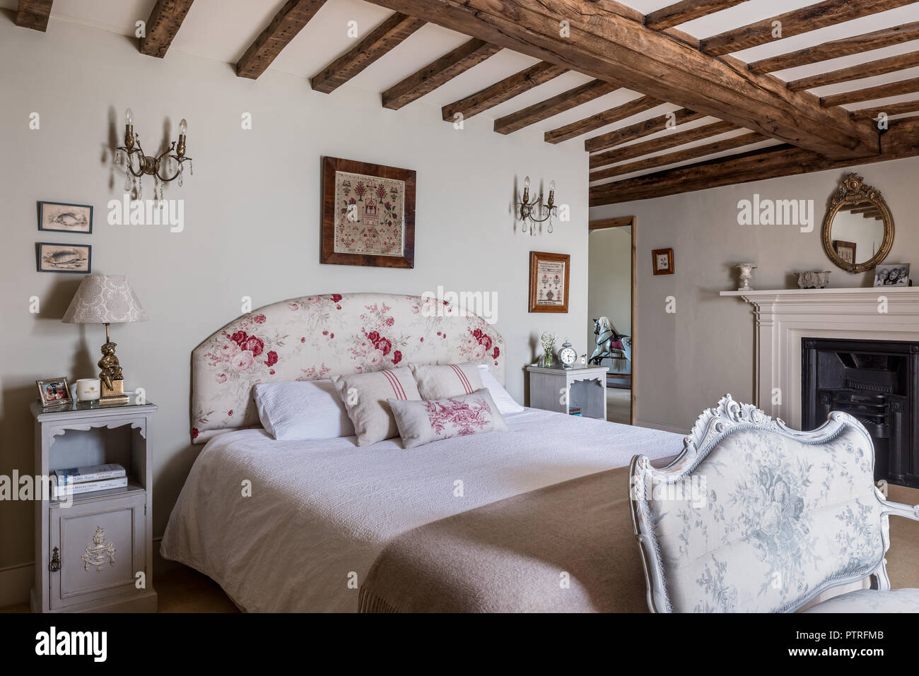 Emboidered folk art above double bed with floral headboard in 16th century farmhouse renovation - Stock Image