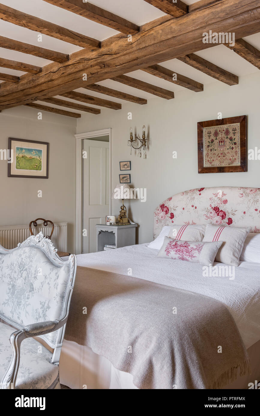 Embroidered folk art above double bed in beamed 16th century farmhouse renovation - Stock Image