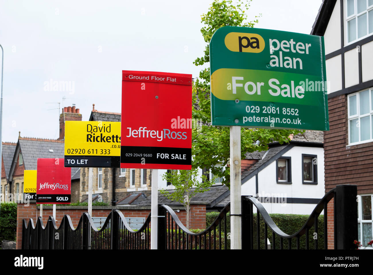 Various estate agents signs for sale outside apartment building in ...