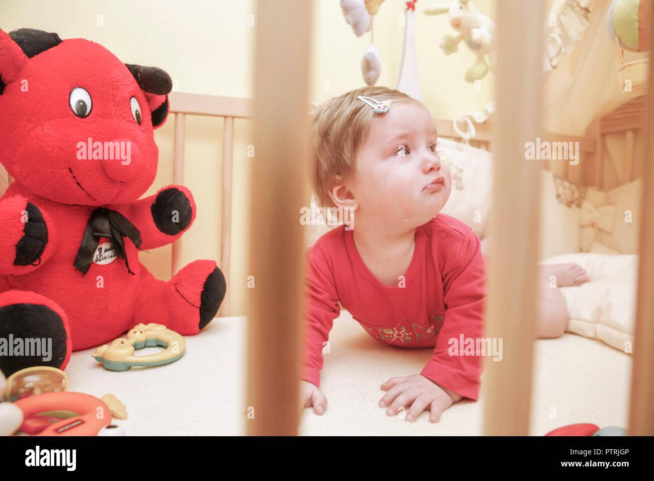 Kinderzimmer, Gitterbett, Kleinkind, liegend, liegen, weinen, Laufstall, Kinderbett, Kind, Baby, Maedchen, blond, Kindheit, traurig, einsam, allein, a - Stock Image