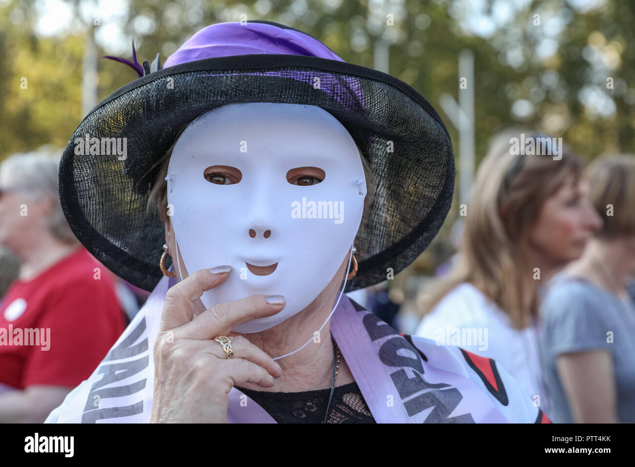 Westminster, London, 10th Oct 2018. A campaigner in suffragette costume and mask shouts for pension equality. Women's pension groups, including the WASPI Campaign, have organised a march from Hyde Park to Parliament Square where several thousand women demonstrate for pension equality in British state pensions. Credit: Imageplotter News and Sports/Alamy Live News - Stock Image