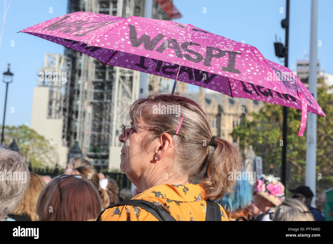 Westminster, London, 10th Oct 2018. A with Waspi umbrella listens to the speakers. Women's pension groups, including the WASPI Campaign, have organised a march from Hyde Park to Parliament Square where several thousand women demonstrate for pension equality in British state pensions. Credit: Imageplotter News and Sports/Alamy Live News - Stock Image