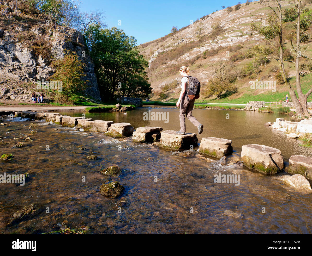 Peak District National Park, Derbyshire, UK. 10th October, 2018. UK Weather Woman crossing the stepping stones on an unusually hot sunny October day in the tourist hotspot of Dovedale in the Peak District National Park, Derbyshire Credit: Doug Blane/Alamy Live News Stock Photo