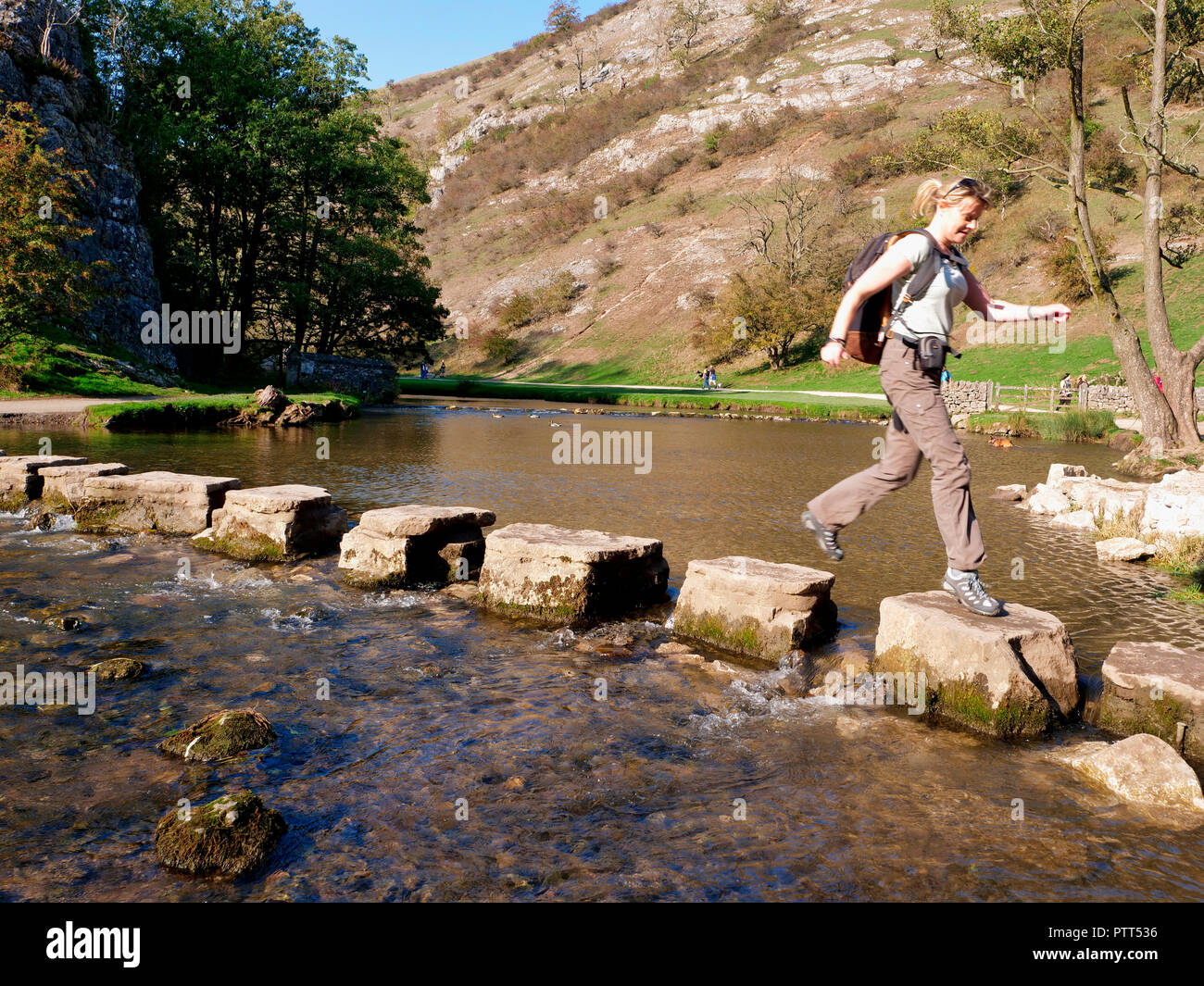 Peak District National Park, Derbyshire, UK. 10th October, 2018. UK Weather Woman crossing the stepping stones on an unusually hot sunny October day in the tourist hotspot of Dovedale in the Peak District National Park, Derbyshire Credit: Doug Blane/Alamy Live NewsStock Photo