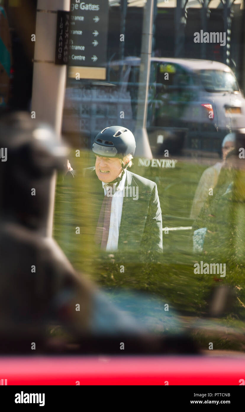 Parliament Square, London, UK. 10 October, 2018. Boris Johnson MP, former Foreign Secretary, seen through the windows of a London bus as he leaves Parliament by bike at mid-day. Credit: Malcolm Park/Alamy Live News. - Stock Image