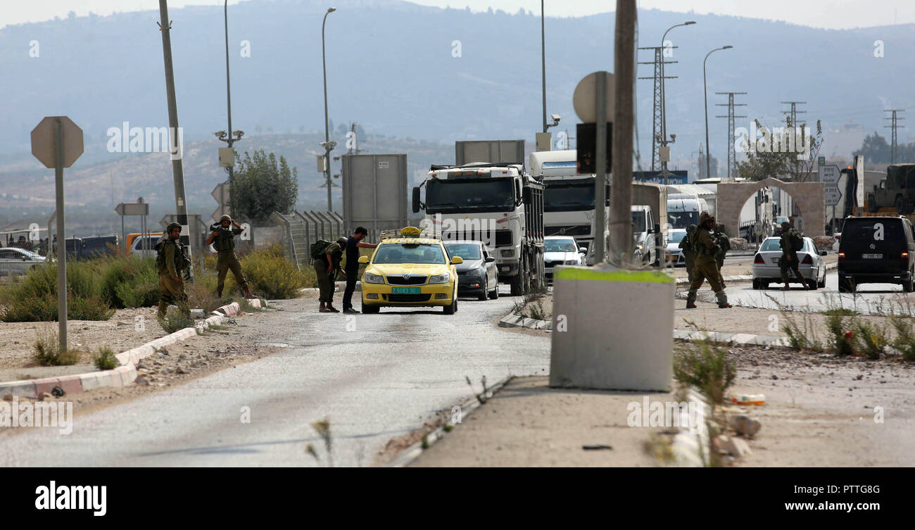 Nablus, West Bank, Palestinian Territory. 11th Oct, 2018. Israeli security forces inspect Palestinian cars at the Huwwara checkpoint, south of the northern occupied West Bank city of Nablus on October 11, 2018. According to Hebrew-language news outlets, that an Israeli settler was injured by Israeli live ammunition after Israeli forces opened fire at a Palestinian, who stabbed one of the soldiers at the Huwwara military checkpoint Credit: Shadi Jarar'Ah/APA Images/ZUMA Wire/Alamy Live News - Stock Image