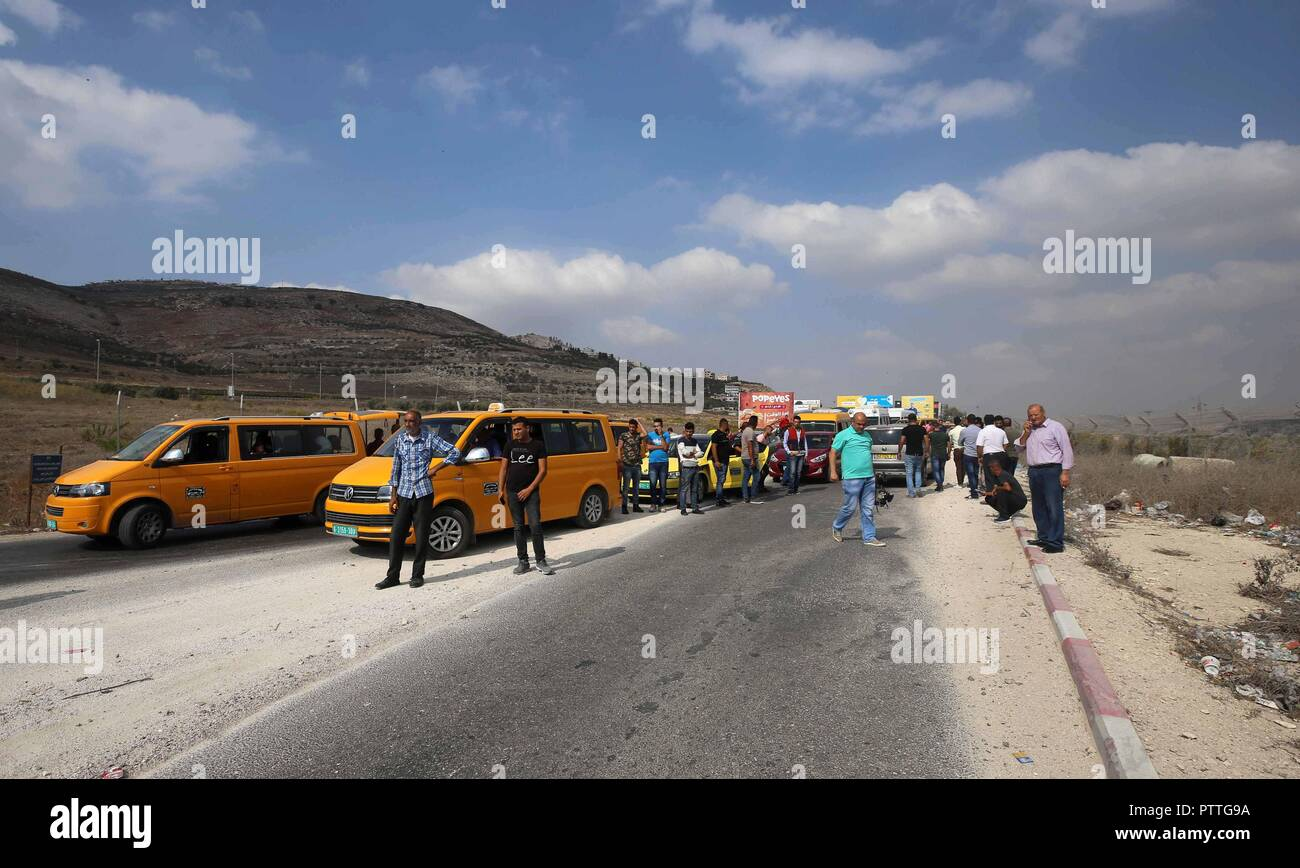 Nablus, West Bank, Palestinian Territory. 11th Oct, 2018. Palrstinians wait as Israeli security forces inspect their cars at the Huwwara checkpoint, south of the northern occupied West Bank city of Nablus on October 11, 2018. According to Hebrew-language news outlets, that an Israeli settler was injured by Israeli live ammunition after Israeli forces opened fire at a Palestinian, who stabbed one of the soldiers at the Huwwara military checkpoint Credit: Shadi Jarar'Ah/APA Images/ZUMA Wire/Alamy Live News - Stock Image