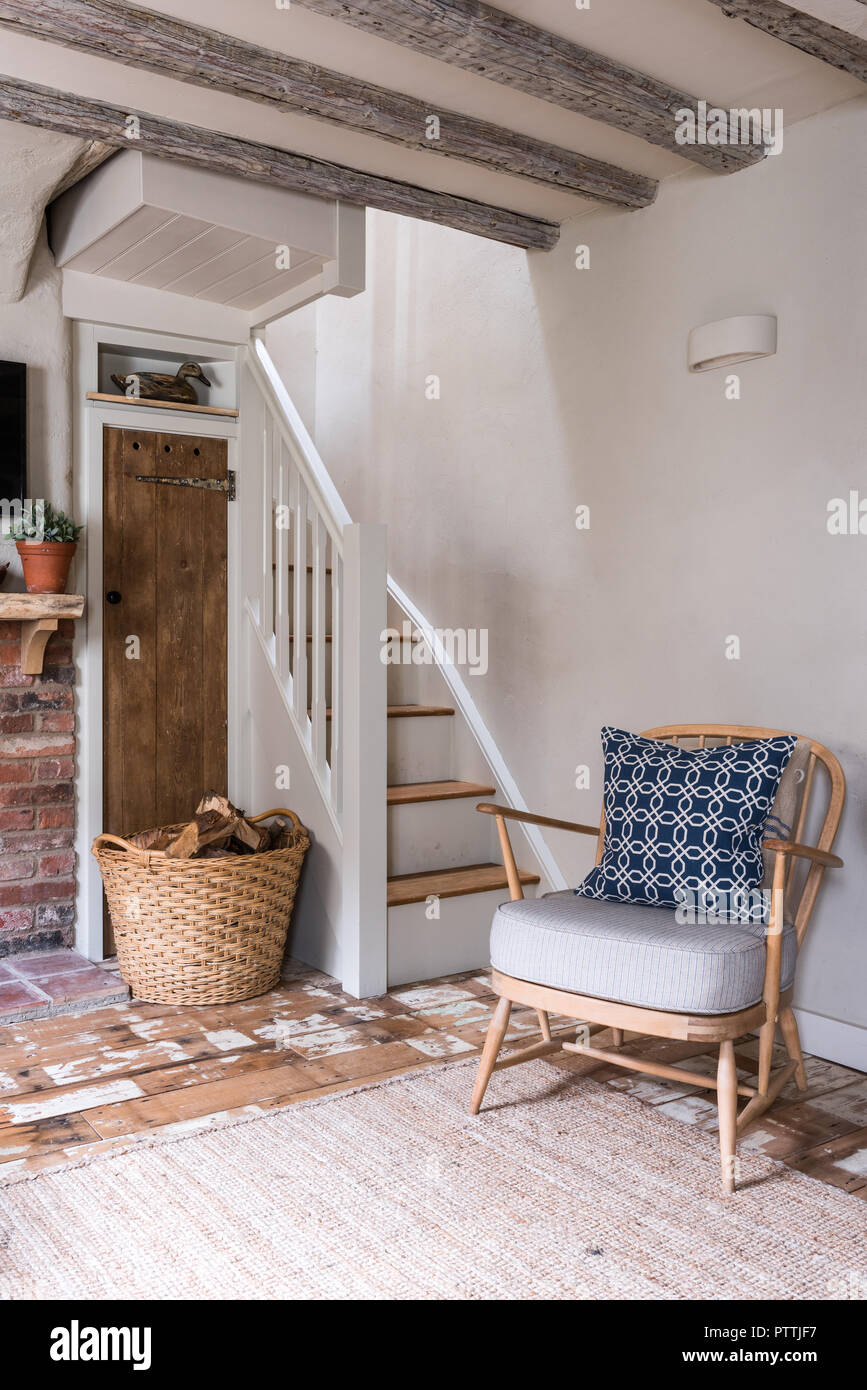 Stripped Ercol-style armchair and log basket with rendered walls - Stock Image