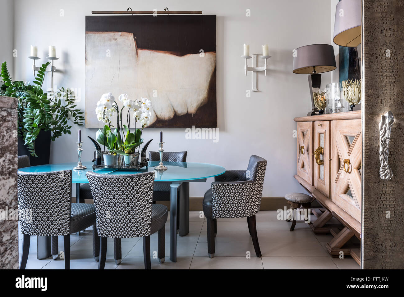 Large Wooden Sideboard And Modern Art In Dining Room With Upholstered Chairs