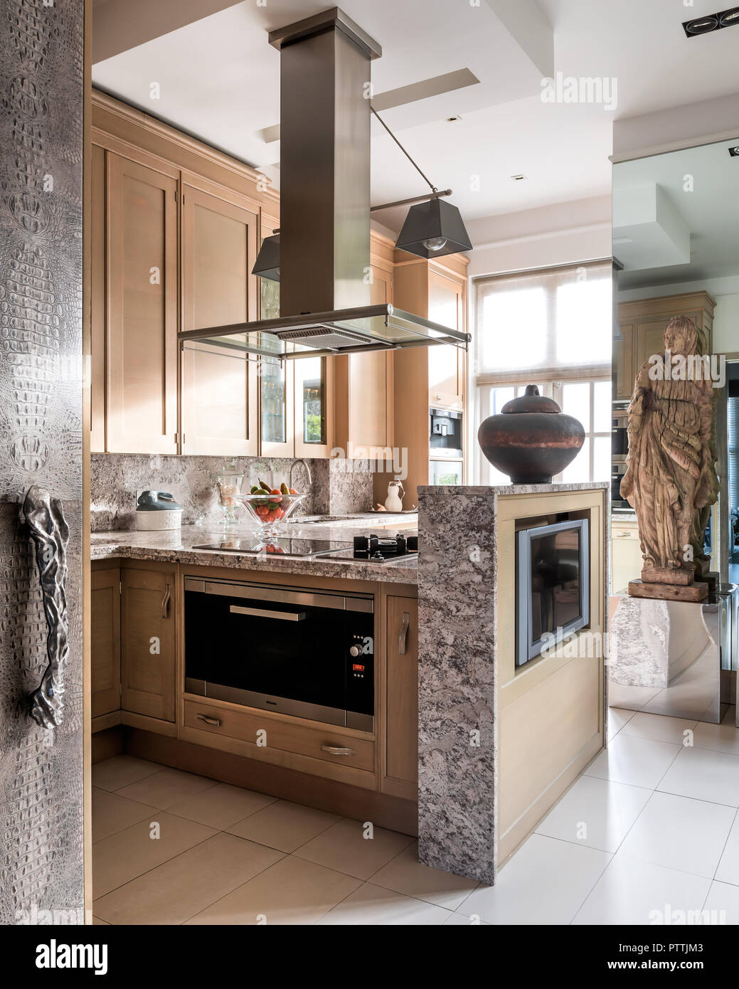 17th century carved oak figure in modern kitchen with stainless steel extractor - Stock Image