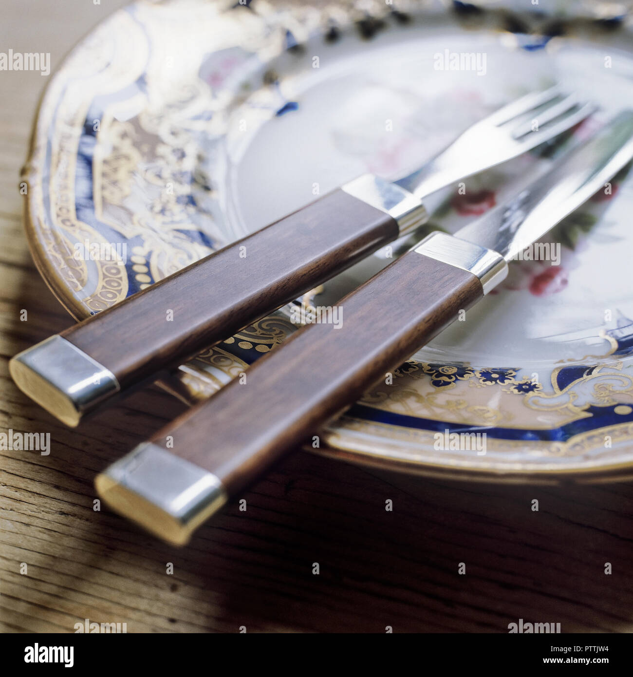Cutlery designed by Lord Snowdon on decorative hand painted plate - Stock Image
