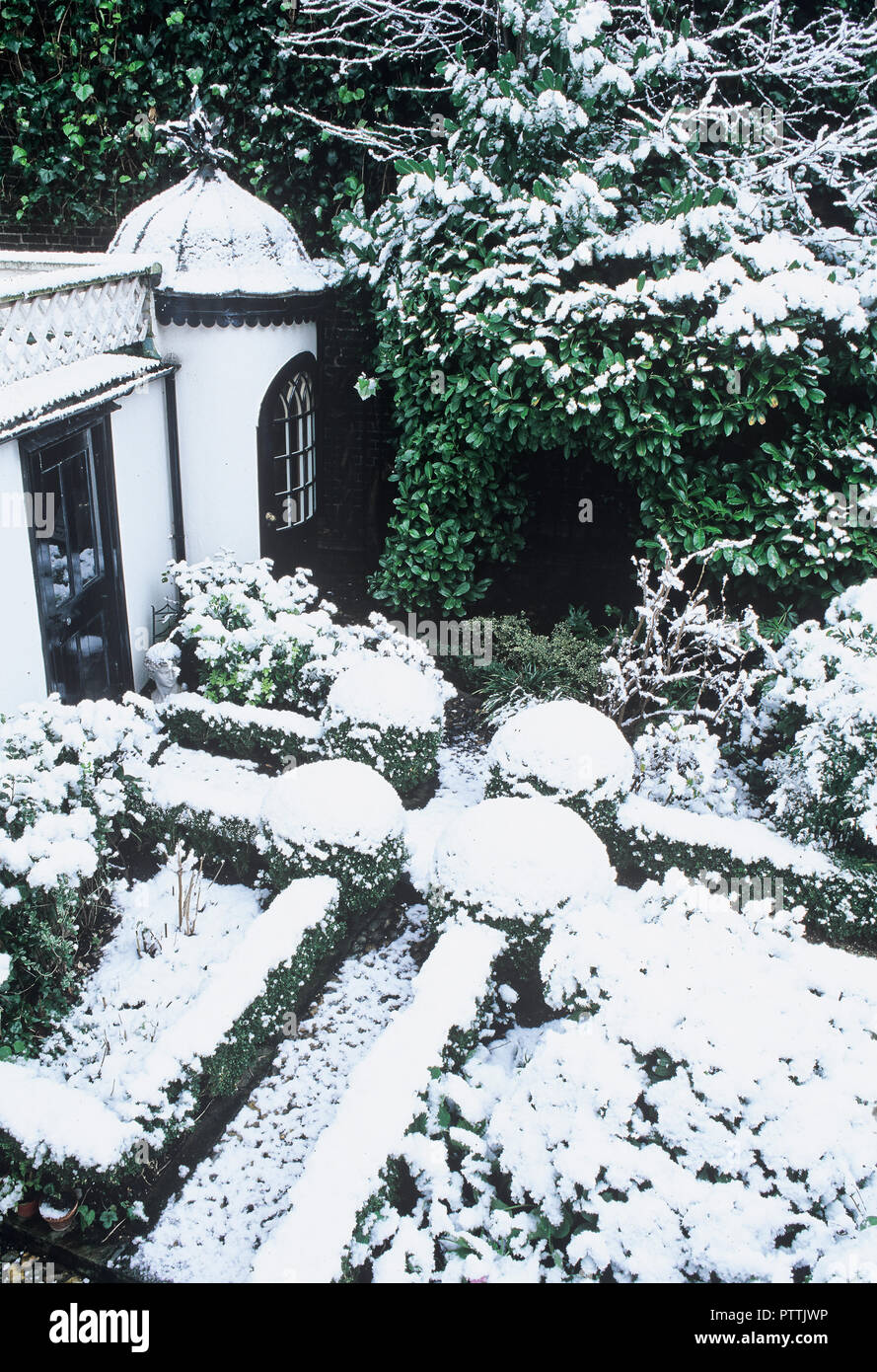 Victorian summerhouse and garden under snow - Stock Image