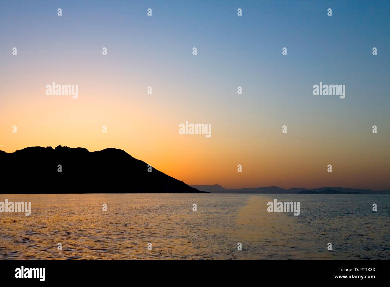 Leaving the island of Othoni, with Corfu beyond, at dawn - Stock Image