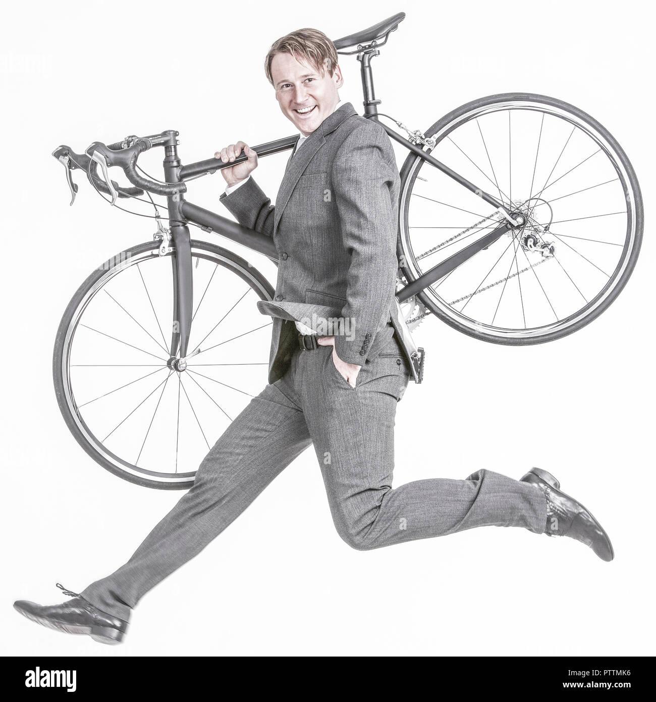 Businessmann traegt sein Rennrad und springt (model-released) - Stock Image