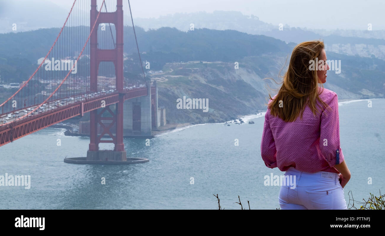 A female tourist standing at the cliff edge at Battery Spencer with the Golden Gate Bridge and San Francisco in the background with the San Francisco Stock Photo