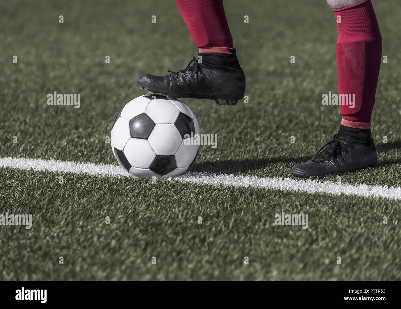 Fussballer haelt Ball mit Fuss, Nahaufnahme (model-released) - Stock Image
