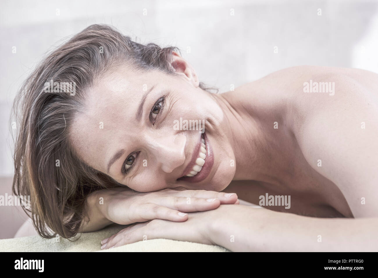 Dunkelhaarige Frau auf Massageliege, Portraet (model-released) Stock Photo